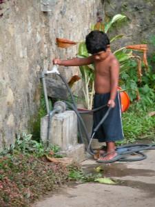 Jongetje in Sri Lanka tapt water af bij een huis in de buitenwijken van Kandy. Foto: Evedien Tukkers.